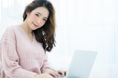Schöne junge asiatische Frau, die an einem Laptop auf einem Laptop arbeitet, der auf Bett im Haus im Winter betrachtet Kamera betrachtet. Frauenlebensstilkonzept