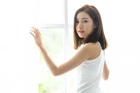 Young joyful Asian woman turn back and holding the curtains open to look out of large light window at home, turning to look and smile at camera.