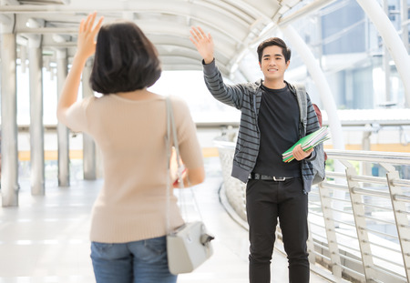 Portrait of a young Asian couple of university students say hello greeting on the street 스톡 콘텐츠