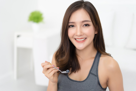 Young Asian woman is resting and eating a greek yogurt with blueberries after a workout  and smiling looking at camera in a living room. Fitness and healthy lifestyle concept.Green healthy food concept.