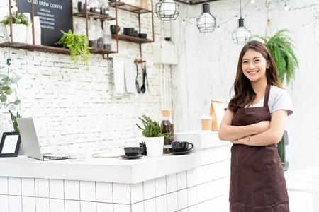 Aantrekkelijke jonge Aziatische mooie Kaukasische barista die in schort bij camera in de teller van de koffiewinkel glimlacht. Opstarten bedrijfseigenaar Concept. Stockfoto