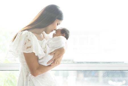 Jeune mère asiatique embrassant un nouveau-né sur le bras à la fenêtre, concept de maternité, image douce de belle famille, concept de fête des mères.