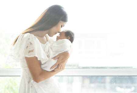 Young Asian mother kissing newborn baby  on the arm her at the window, maternity concept, soft image of beautiful family, mother's day concept. Stock Photo