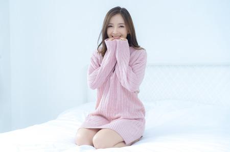 Mujer asiática hermosa joven en ropa rosada tejida caliente que lleva a cabo sus manos debajo de la barbilla en casa. modelo . Otoño, invierno, con espacio de copia.