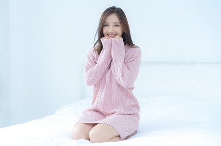 Young beautiful Asian woman in warm knitted pink clothes holding her hands underneath the chin at home. fashion model . Autumn, winter,with copy space