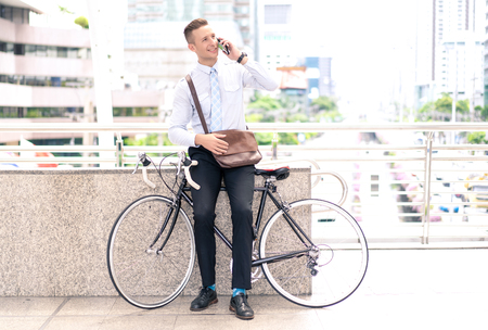 Confident young businessman using phone, looking away and smiling on his bike, standing city. Stok Fotoğraf