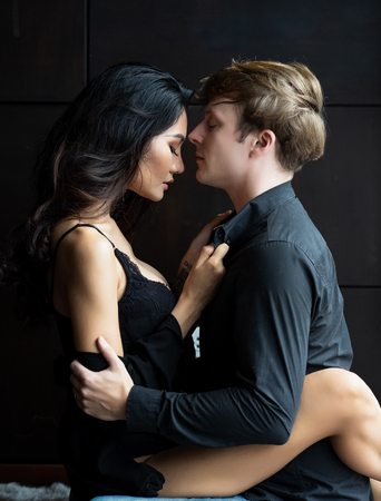 Handsome young man and sexy undressed young woman in black lingerie are hugging in room,so tender, romantic, tempting, sensual. Banque d'images