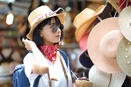 Urban city lifestyle hipster asian woman wearing summer clothes and trendy sunglasses shopping for straw beach hat trying on in outdoor market shop store on downtown street of Bangkok City, Thailand, Concept Travel