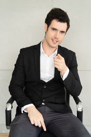Smart businessman pointing at you while sitting in chair at plaster texture background