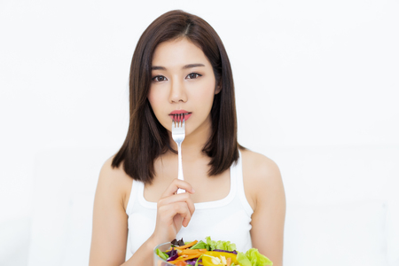 Portrait of young Asian woman eating healthy salad and pressing fork to her lips and looking at camera isolated on white white background Stockfoto