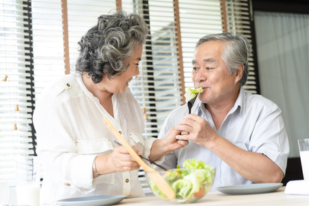 Beautiful loving senior Asian couple eating fresh vegetable salad. Wife feeding husband and having fun at home. Looking softly on each other. Stock Photo