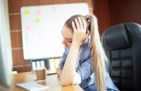 Feeling sick and tired. Frustrated young woman with headache while sitting at his working place in office.