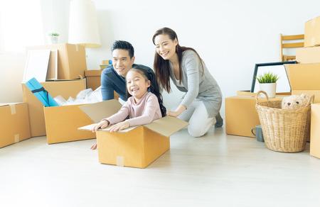 Felice giovane famiglia asiatica di tre persone che si divertono a muoversi con scatole di cartone nella nuova casa al giorno del trasloco. Giorno del trasloco e concetto di consegna espressa.