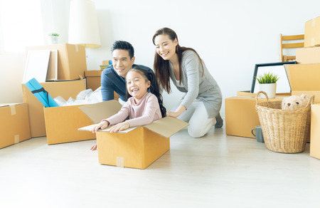 Happy young Asian family of three having fun moving with cardboard boxes in new house at moving day. Moving house day and express delivery concept.