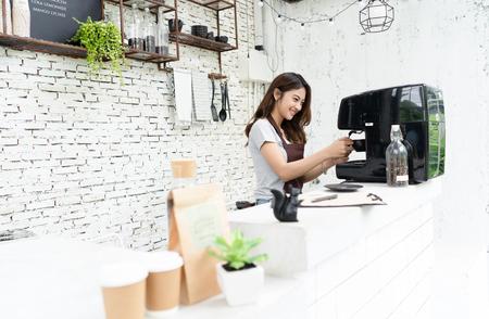 Jonge mooie barista vrouw in een schort kopje koffie bereiden voor de klant in de coffeeshop. Vrouw startende ondernemer en MKB-concept.