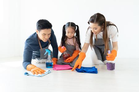 Felice giovane famiglia asiatica di tre persone che puliscono il soggiorno di casa durante il fine settimana. Piccolo aiutante carino. Lavori domestici di famiglia e concetto di famiglia.