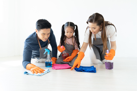 Happy young Asian family of three cleaning their home living room at weekend.Cute little helper. Family housework and household concept.