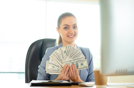Happy brunette woman  with many dollars near laptop in office.