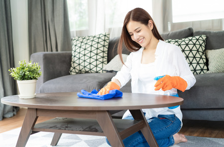 Beautiful young Asian woman wearing Protective Gloves Cleaning desk by spraying Cleaning Products and wipes  in living room.