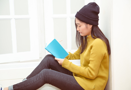 Young woman in winter clothes sitting at the door thinking and writing Stock Photo