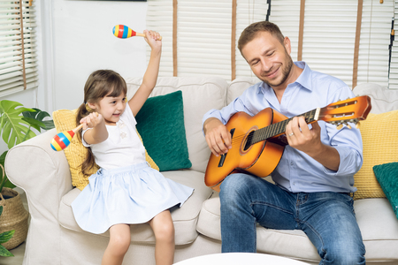 Happy Fathers day.Funny portrait of smiling father playing guitar and her daughter holding maracas dancing and sitting sofa at home, Activity family love and liftstyle Concept Imagens