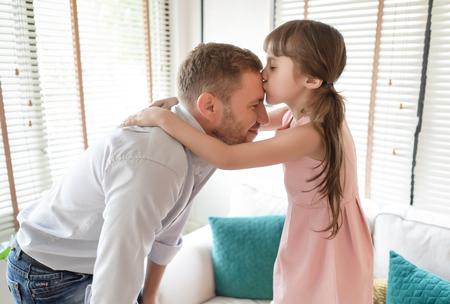 Alles Gute zum Familien- und Vatertag. Porträt eines kleinen Mädchens, das ihren Vater auf die Stirn küsst. Liebevolles Kind umarmt und küsst ihren Vater. Standard-Bild