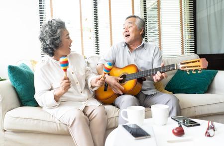 Amoureux dans un salon. Portrait drôle d'un homme âgé souriant jouant de la guitare et de sa femme tenant des maracas dansant et assis sur un canapé à la maison, Activité familiale amour et concept liftstyle.