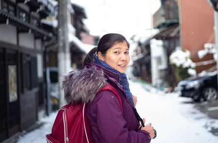 Tourist traveler Asian woman is in the winter on a snowy road and looks at Takayama old Town Street in winter snow and looking at camera.