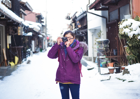 Beautiful Asia girl in warm clothes photographer takes pictures at Takayama Old Town Street in winter snow.