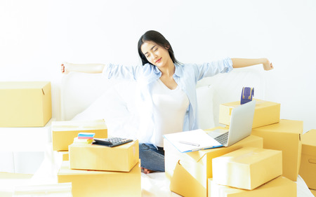 Tired young casual Asian business woman working small business online packing her sleep, Overwork load packing box,Shipping shopping online small business entrepreneur SME or freelance concept;
