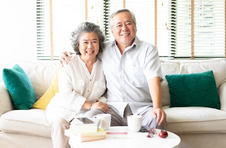 Porträt eines glücklichen asiatischen Seniorenpaares, das sich zu Hause auf dem Sofa entspannt, während die Frau ihren Ehemann umarmt und beide in die Kamera lächelt Standard-Bild
