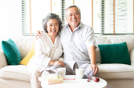 Portrait of a Happy Asian Senior couple relaxing at home on the sofa with the wife hugging her husband  both smiling at camera Stockfoto