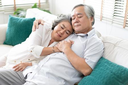 Älteres Paar entspannt zusammen schlafen auf dem Sofa im Wohnzimmer zu Hause. Entspannen und Lifestyle-Konzept. Standard-Bild