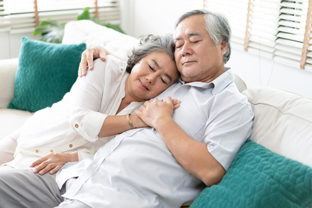 Senior couple relaxing sleeping together on sofa in living room at home. Relax and Lifestyle Concept.