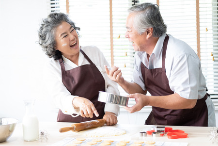 Happy family senior couple are sprinkling the dough with flour and laughing while baking cookies at home kitchen.  Baking and cooking with wife at home.
