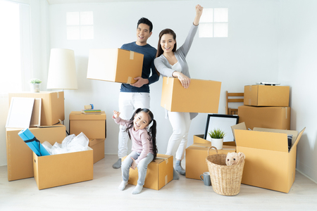 Gelukkige jonge Aziatische familie verhuist de dozen naar een nieuw huis. Bewegend concept.