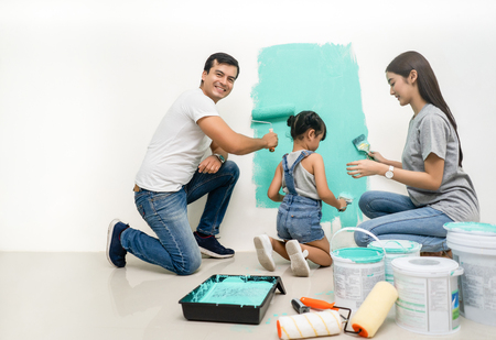 Happy family renovating their new home.Father sitting near daughter, smiling painting with a roller and looking at camera.