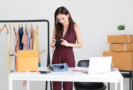 Jeune femme asiatique décontractée travaillant dans une petite entreprise prenant une photo du produit sur un appareil photo numérique pour la vente sur le site Web du bureau à domicile. Startup Propriétaire d'une petite entreprise, vente en ligne, commerce électronique, livraison, concept de travail indépendant.
