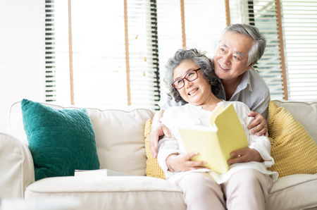 Happy senior couple are sitting on the couch together and reading a book and looking sideways in living room at home. Stockfoto