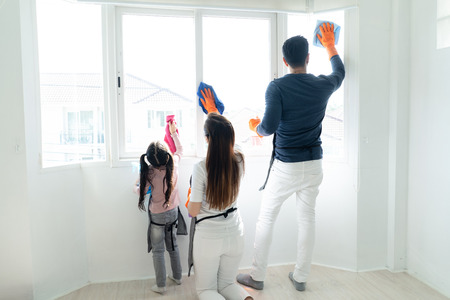 Back view of Asain family doing the house cleaning. Young family washing windows together in living room. Family housework and household concept. Banque d'images