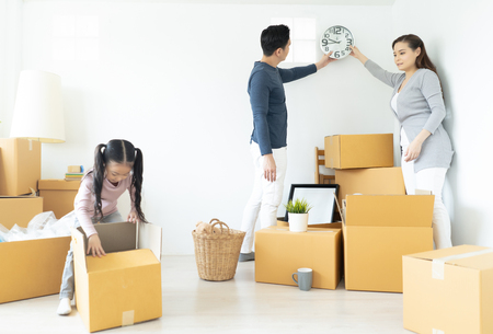 Happiness young Asian family unpacking cardboard boxes and moving into a new home.Moving house day and express delivery concept. Stock Photo