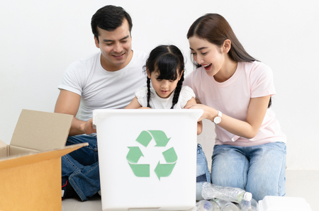 Happy multiethnic family siblings having funsorting segregating household waste at home.Lifestyle - ecological education and awareness concept Foto de archivo
