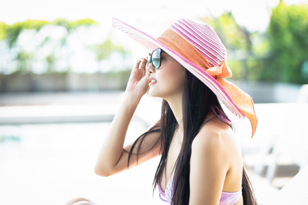 Side view beautiful Asian woman in hat relaxing enjoying sunny weather by tropical swimming pool. Fashionable portrait. Summertime vacation concept