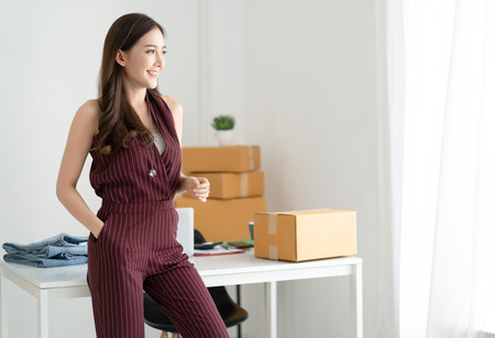 Young Asian casual woman working small business owner standing looking in distance thinking of future career opportunities and smiling at home office. Start up small business entrepreneur SME,Online selling, e-commerce, Freelance Startup Home office