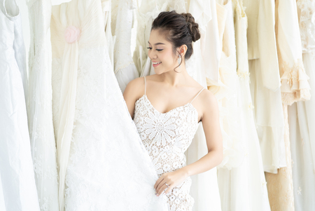 Beautiful Asian bride is smiling while choosing some wedding dress in modern wedding salon.Wedding day moments.