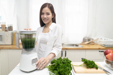 Young smiling Asian woman making smoothie with fresh greens in the blender in minimalist kitchen at home and looking at camera. Healthy vegetarian smoothie for weight loss and detox. Healthy eating lifestyle concept