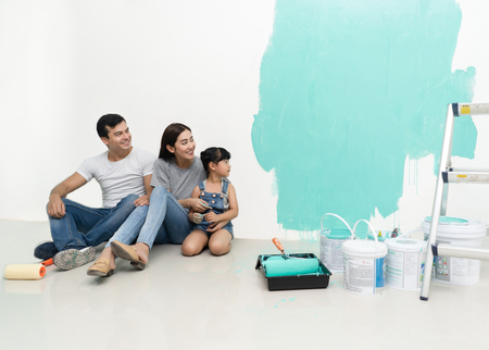Happy multiethnic family renovating their new home, they are sitting together and smiling and look at the colors on the walls with happiness.
