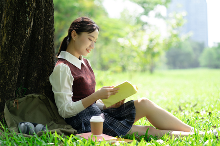 Portrait of beautiful smiling Asian woman sitting on green grass in park and relaxing while reading a book.