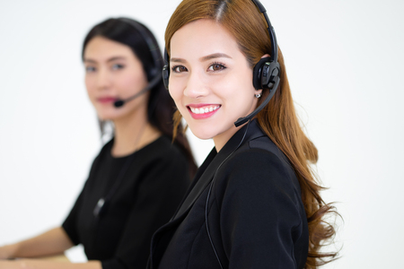 Call center operators at work. Side view of beautiful young Asian business woman in headsets using laptops while working in office. Girl is looking at camera