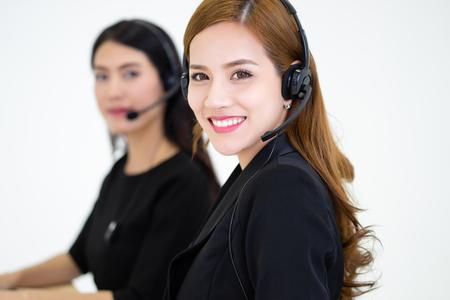 Operadores de centros de llamadas en el trabajo. Vista lateral de la joven y bella mujer de negocios asiática en auriculares con ordenadores portátiles mientras trabajaba en la oficina. Chica está mirando a la cámara